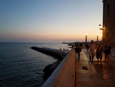 Sitges, Spain - September 20, 2018: Sitges night scene with a view of the sea with people walking.
