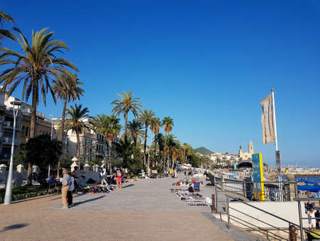 Sitges, Spain - September 20, 2018: Sitges promenade scene on a sunny clear summer day with palm trees lining the promenade and people walking. Editorial