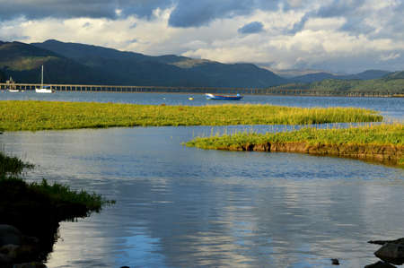 Marsh, estuary with boats, Barmouth bridge and mountains forming the Welsh landscape.
