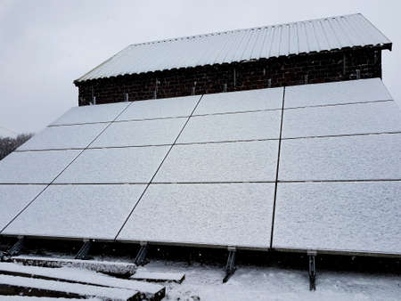 Winter day with snow-covered solar panels at the side of an outbuilding. Banque d'images
