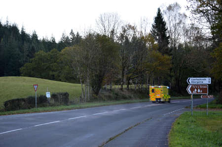 North Wales, United Kingdom - 10/29/2018: Ambulance moving fast out of shot on a country road. Éditoriale