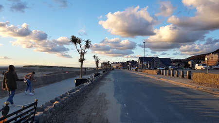 Barmouth, Wales, United Kingdom - 10/30/2018: Barmouth promenade during sunset with interspersed clouds and two people in the foreground. Éditoriale
