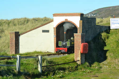North Wales, United Kingdom - 10/30/2018: Fairbourne steam train emerging from a tunnel. Éditoriale