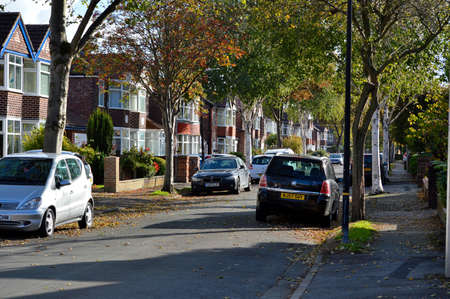 Manchester, England, United Kingdom - 10/22/2018: Autumn urban street with houses and trees lining the road and autumnal leaves on the ground.