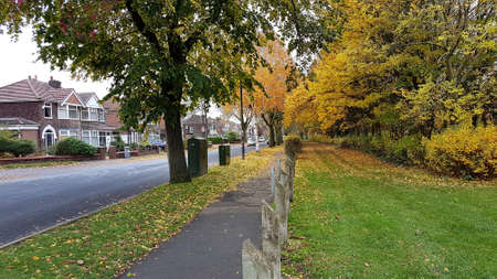 Manchester, England, United Kingdom - 10/22/2018: Urban residential street facing a park with Autumn trees. Éditoriale