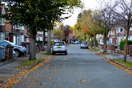Manchester, England, United Kingdom - 10/22/2018: Urban residential street with cars parked on an Autumn day in the UK.