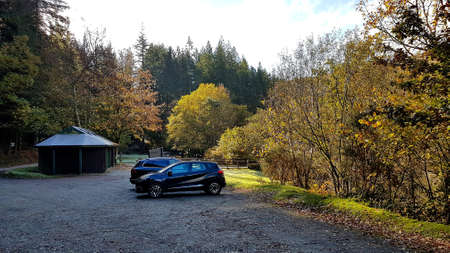 North Wales, United Kingdom - 10/29/2018: Welsh forest car park with a couple of cars parked and a small rustic building surrounded by trees.
