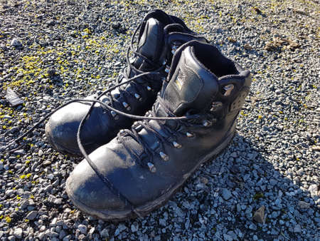 North Wales, United Kingdom - 01/17/2019: Well-worn hiking boots on gravel. Éditoriale