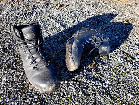 North Wales, United Kingdom - 01/17/2019: Mud covered hiking boots on gravel. Éditoriale