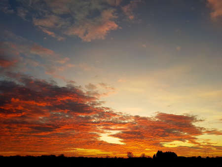 Spring sunset, dusk horizon with colourful sky of blue, orange and yellow shades with silhouette landscape.