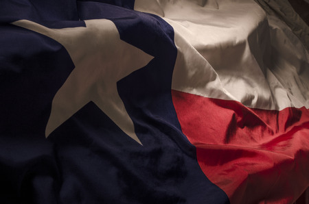 close up view of the Texas Lone Star flag isolating the three separate colors and the single star amongst shadow, high lights and waves 写真素材