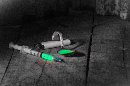Parafernalia de abuso de drogas en el suelo sucio y húmedo de una trastienda Foto de archivo - 87341819