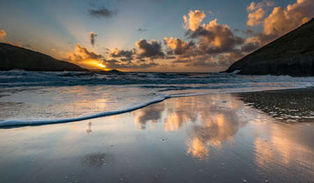 wales: Sunset reflected in shallow water with foam on the beach in Mwnt, Wales, UK. September. Stock Photo