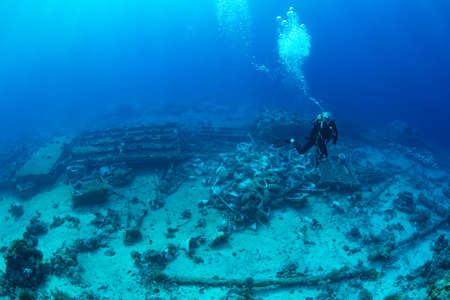 Diver next to Yolanda wreck with toilets scattered on seabed. Red Sea. November Фото со стока