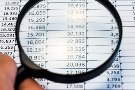 Business Analysis Image-magnifying glass on graphs and spreadsheet