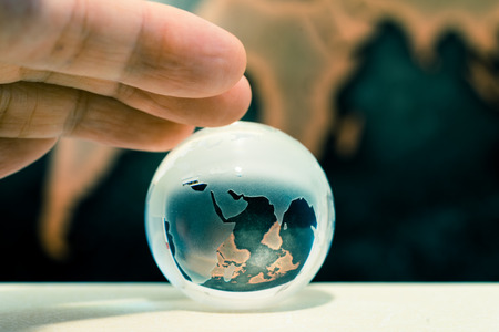 Crystal globe on books against grunge world map
