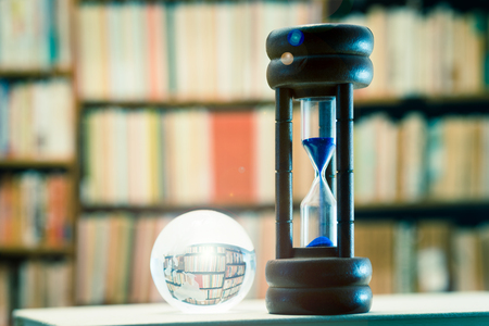 With lens flare, hourglass against book shelf