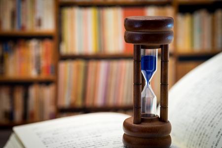 Hourglass against book shelf