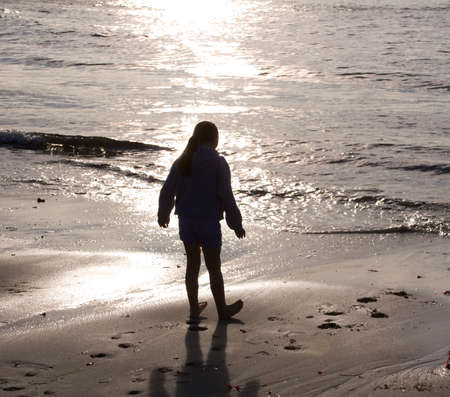 a young girl silhouetted on the beach photo