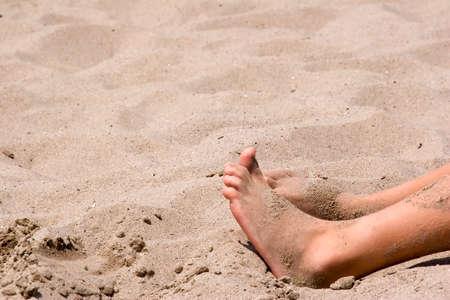 zanderige voeten in de zon op het strand Stockfoto
