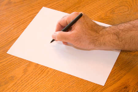 a hand poised over a blank sheet of paper photo