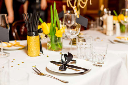 sequins: Birthday guests table setting with fresh flowers in black and gold style, indoor.
