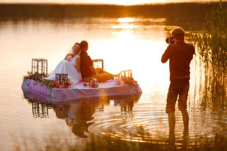 Ślub fotograf w akcji, biorąc obraz Narzeczeni siedzi na tratwie. Lato, Zachód słońca. Zdjęcie Seryjne