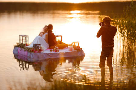 mode: Wedding photographer in action, taking a picture of the bride and groom sitting on the raft. Summer, sunset. Stock Photo