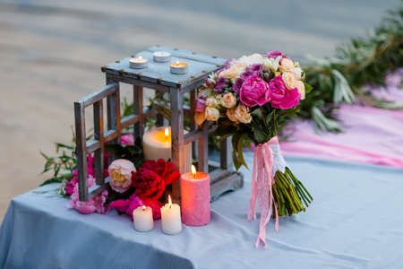 Beautiful, delicate bridal bouquet among decoration with candles. Stock Photo