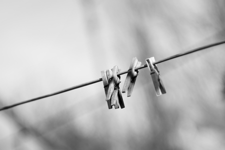 Wooden clothespins on a rope. Monochrome photo.