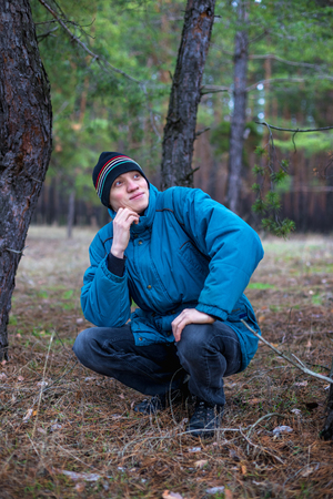 A rural guy posing in a pine forest in the autumn time
