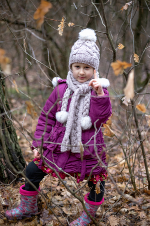 Little cute girl posing in autumn forest. Banco de Imagens