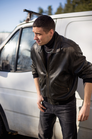 A young guy of criminal appearance in a black leather jacket stands near an old white van