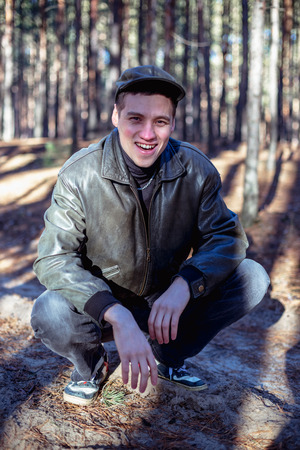 A guy in a leather jacket and cap sits on a road in a pine forest