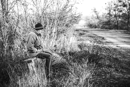 A young man sits on an old bench at a rural bus stop in the autumn time. The concept of waiting for a bus to a better life.