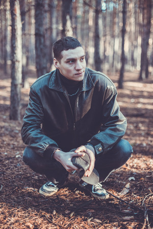 A young man of criminal appearance in a black leather jacket posing in an autumn forest