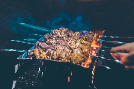 Grilled kebab cooking on metal skewers (grill). Roasted meat cooked at barbecue with smoke. Close up BBQ fresh pork meat chop slices. Traditional eastern dish, shish kebab.