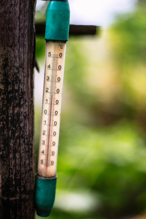 Old thermometer hanging in the yard of the rural house