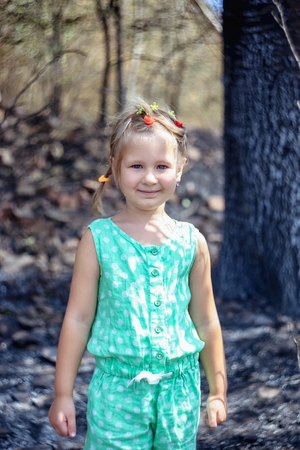 Portrait of a little girl in the forest after a fire