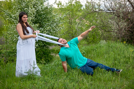 Husband tries to escape from a pregnant wife Stock Photo