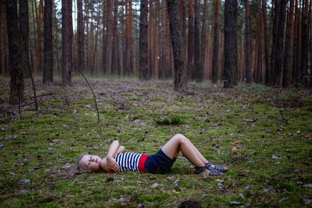 Beautiful little girl in the pine forest in summer