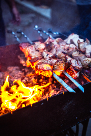 Grilled kebab cooking on metal skewers (grill). Roasted meat cooked at barbecue with smoke. Close up BBQ fresh pork meat chop slices. Traditional eastern dish, shish kebab. Grill on charcoal and flame, picnic, street food. Toned, style, classic photo.