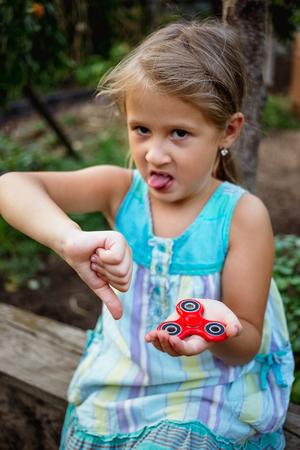 Small cute rural girl doesnt really like fidget spinner