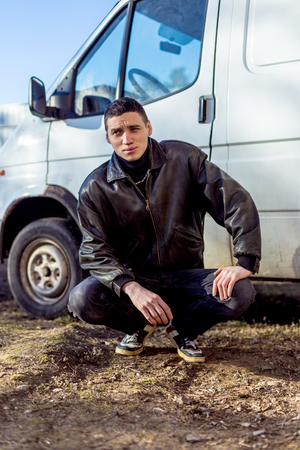 A young guy of criminal appearance in a black leather jacket stands near an old white van. Stock Photo