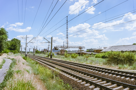 A blue sky with feathery clouds, a green grass along the railway and an old dilapidated plant in the background. Stock Photo