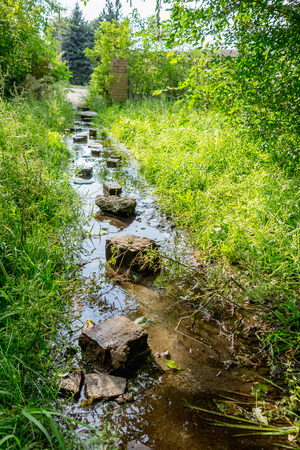 Flooded path in the summer. The concept of daily obstacles. Overcoming a difficult path to achieve the intended goal. Difficulties on the way to success. Stock Photo