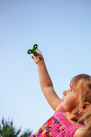 Little girl in the countryside holds a spinner in her hand Stock Photo