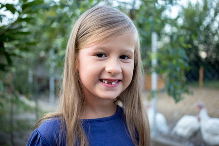 Young little girl without a front tooth in the countryside