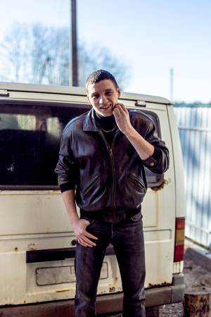 A young guy of criminal appearance in a black leather jacket stands near an old white van. Фото со стока