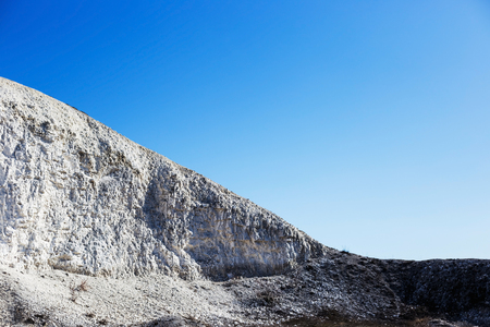 Large chalky mountain and blue sky without clouds. Stock Photo